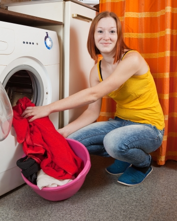woman putting clothes into washing machine and looking at camera photo