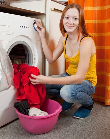 Young woman loading the washing machine in kitchen Stock Photo - 8769663