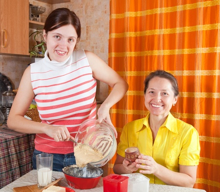 douther: Two women making celebration cake in the kitchen at home Stock Photo