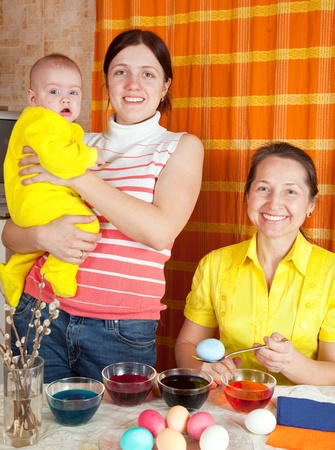 Happy family coloring easter eggs in kitchen Stock Photo - 8770000