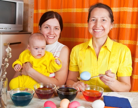 Happy family coloring easter eggs in kitchen photo