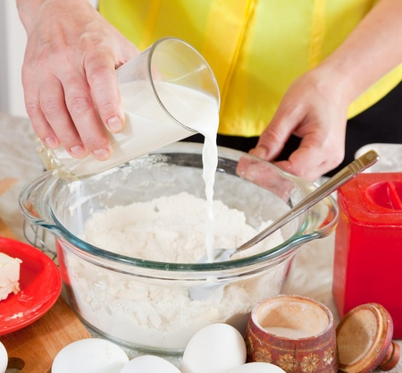 Closeup of cook hands pouring milk into flour  photo