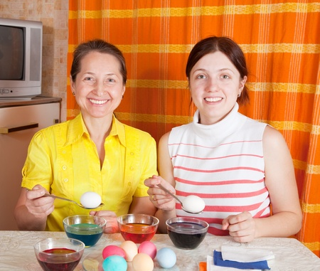 Daughter and mother coloring eggs for Easter holiday photo