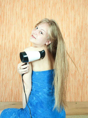 Girl using hairdryer  in home interior photo