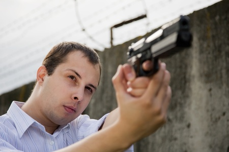 young man aiming a black gun against the prison wall Stock Photo - 8771218