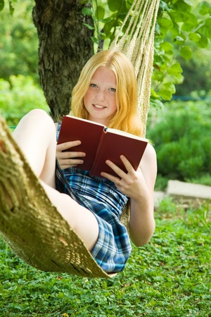 young girl reading book on hammock outdoor photo