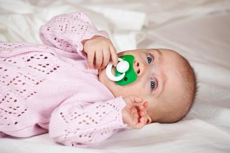 babygro:  5 months baby girl laying on white sheet Stock Photo