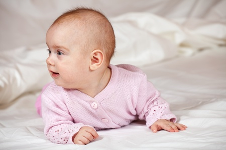 babygro: Baby girl of 5 months old on white sheet