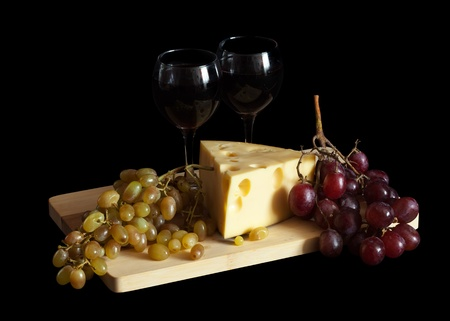Grapes and cheese with glasses of red wine on black background photo