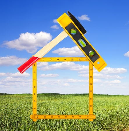 house concept build with tools over summer landscape photo