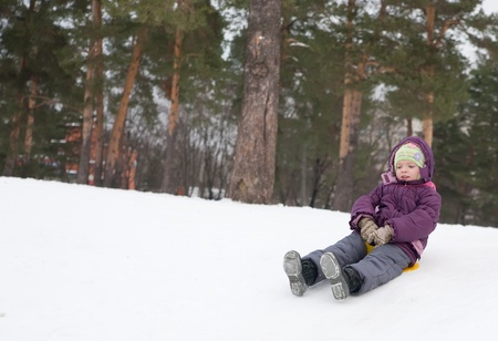 Little child sliding in the snow  against tree photo