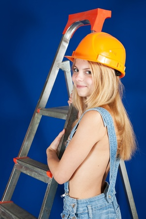Sexy  female  builder  with stepladder over blue Stock Photo - 8886772