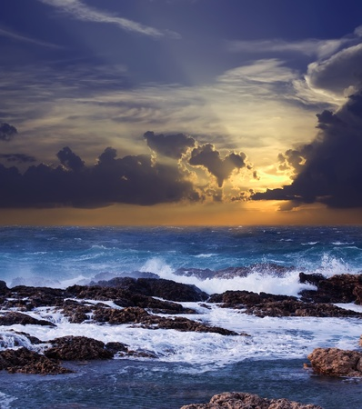 Sea wave breaking against coast  rock in sunset time Stock Photo