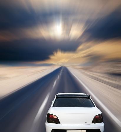 White car on desert road under blue sky Stock Photo