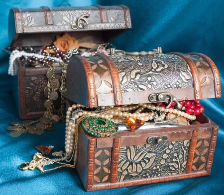 ear ring: Two wooden treasure chests with valuables on blue textile Stock Photo