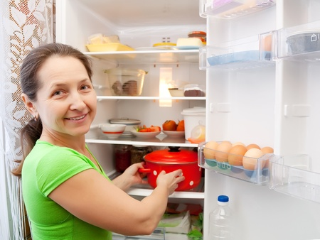 Mature woman putting pan into fridge  at home photo