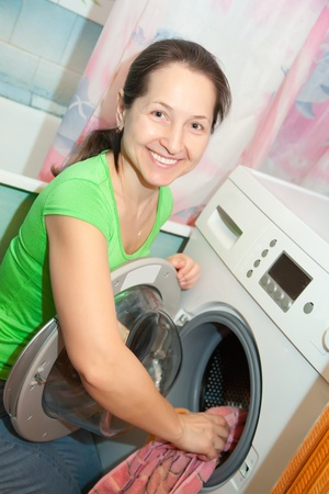 Mature woman with washing machine at her home Stock Photo - 8886980