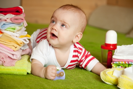 babygro: Happy baby girl with heap of babys things  Stock Photo