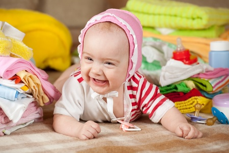 babygro: baby girl with stacked of childrens clothes