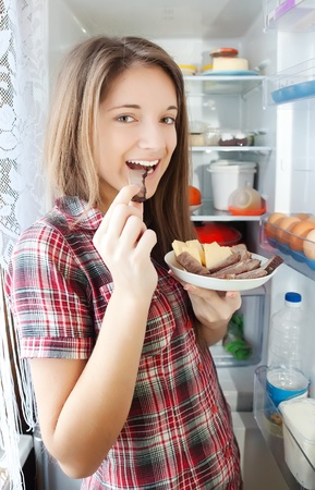 Teenager girl eating  meat from  fridge  at home photo