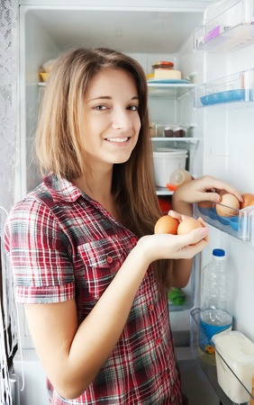 Teenager girl putting eggs into refrigerator  at home photo