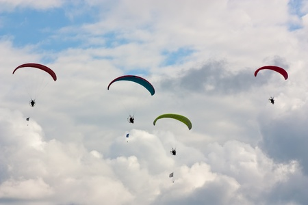 parapendio: Four paragliders  soaring against cloudy sky  ib summer Stock Photo