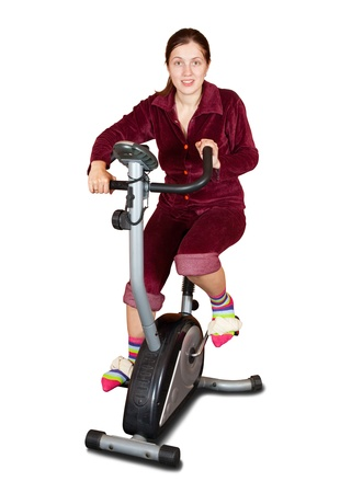 Girl workout on stationary bicycle. Isolated on white photo