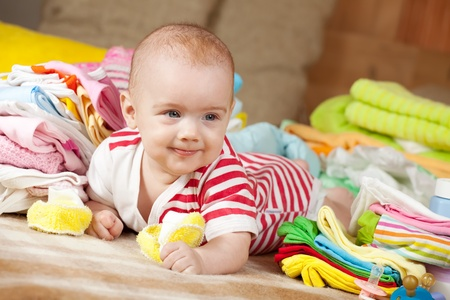 Happy baby girl with heap of babys wear