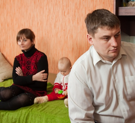 couple arguing: young marriage quarreling at home. Their daughter sitting between them Stock Photo