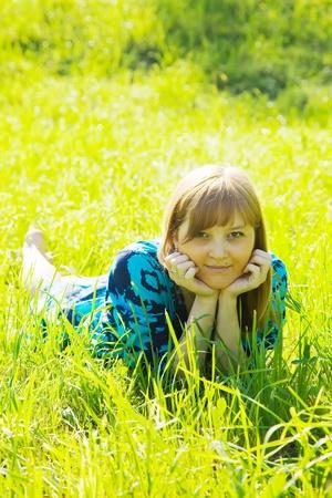 Pretty teen girl is lying on meadow photo