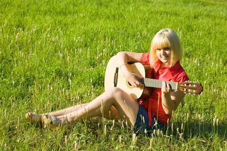 Teenager girl with guitar against green grass photo