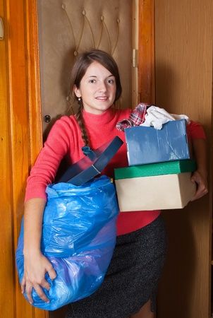 out door: Young woman putting out the garbage at home Stock Photo