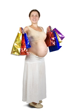 8 months pregnancy: pregnant woman holding shopping bags. Isolated in full length on white background.