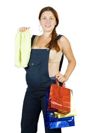 children's wear: pregnant woman with shopping bags and childrens wear over white Stock Photo
