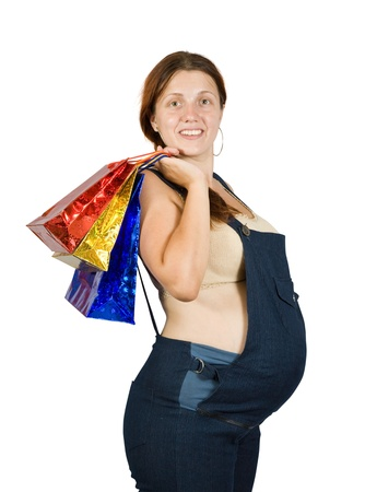 8 months pregnancy: pregnant woman with shopping bags. Isolated over white background