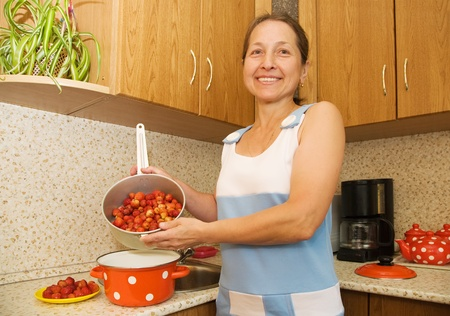 Woman in the kitchen with red strawberry photo