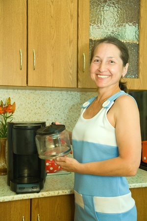 percolator: elderly woman making coffee using espresso machine Stock Photo