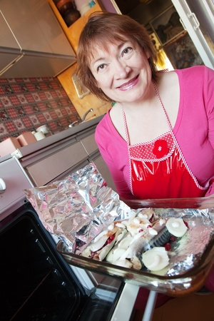 Woman putting mackerel with cranberry in griddle into oven