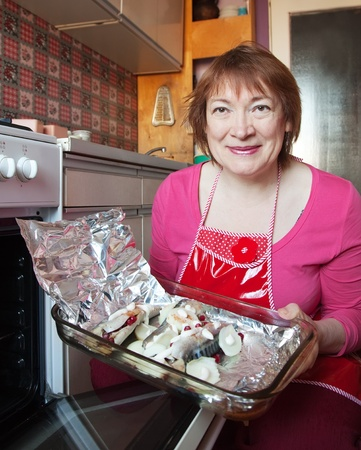 bakeoven: Woman putting mackerel with cranberry in griddle into oven