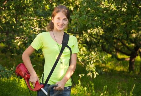 Girl works with hand grass-cutter in garden photo