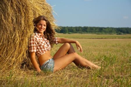 Pretty girl resting on fresh straw bale photo