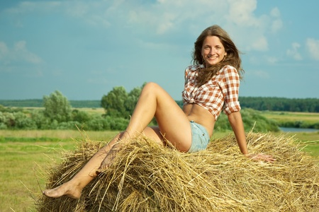 checked shirt: Pretty girl in checked shirt resting on straw bale Stock Photo