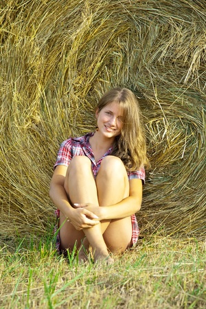 country girl on fresh straw at field photo