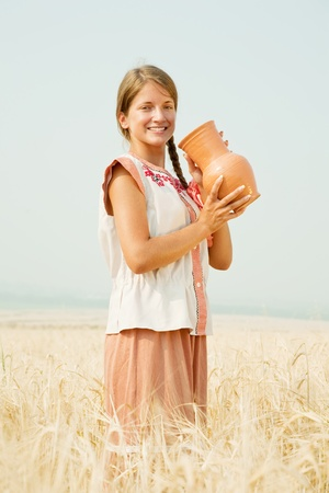 Young girl  in traditional clothes   with jug at cereals field in summer photo