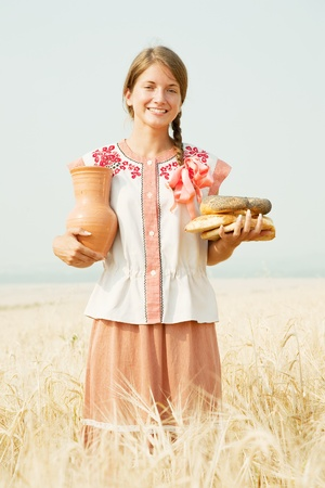 Girl in traditional clothes with bread and jug at rye field Stock Photo - 8996317