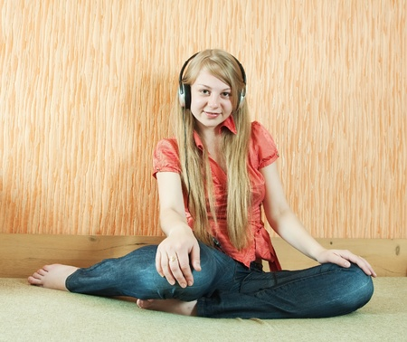 househould: Young   happy girl listening music in headphones on  couch