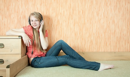 househould: Young beautiful happy girl listening music in headphones on couch Stock Photo
