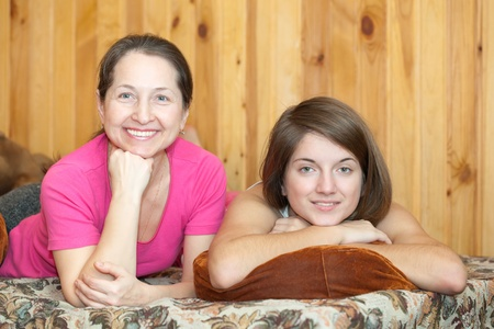 Happy mother with her teenager daughter  laying on sofa photo