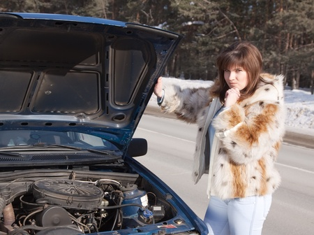 woman looking under the car hood in winter day photo