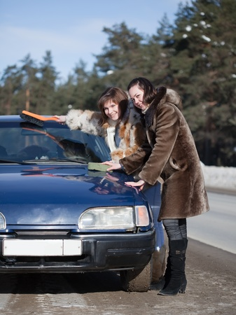 Two happy women cleaning car in winter day Stock Photo - 8996924